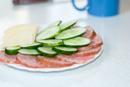 Cut cheese, sausage and cucumber in a plate. photo