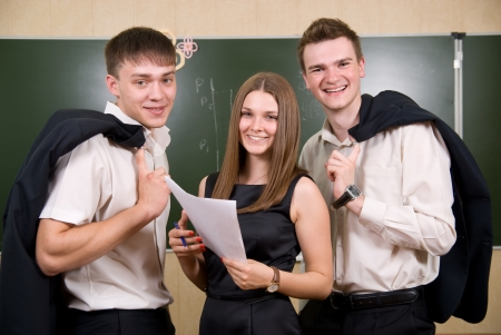 succeeding: Three young succeeding the businessman against a board. All smile Stock Photo