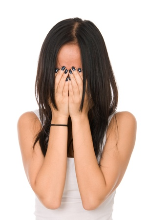 tormented: Girl in despair shuts face with hands.Isolated on white background