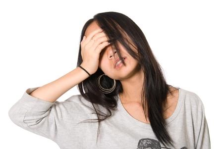 blindly: Retrato de ni�a cansada a ciegas con una mano sobre un fondo blanco forehead.On.