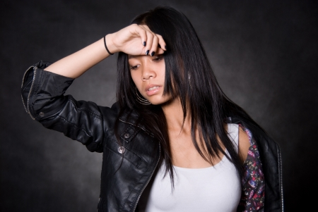 Portrait of the tired girl with a hand on a forehead.Asian girl on a black background in a leather jacket photo