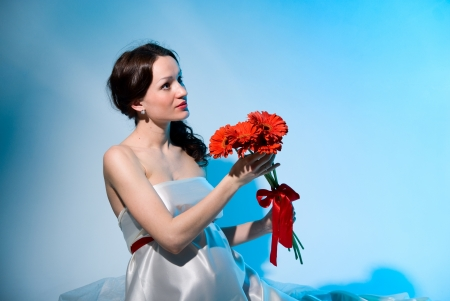 Pregnant woman holds red flowers on stretched hands.Blue background photo
