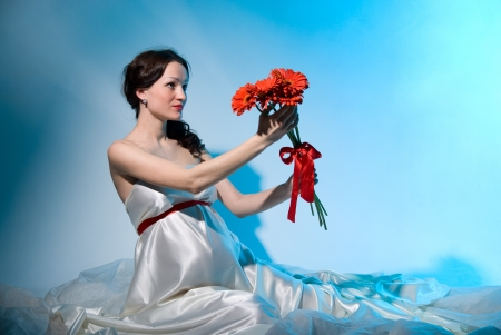 Pregnant woman holds flowers on outstretched arms on a blue background photo