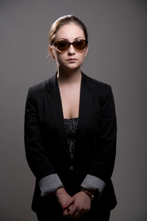 Portrait of a beautiful woman wearing sunglasses on a gray background photo
