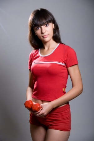 Beautiful  girl with dumbbells. Isolated against gray background Stock Photo - 15484279