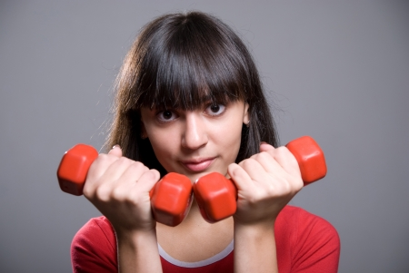 Young woman with dumbbells, isolated against gray background Stock Photo - 15484269