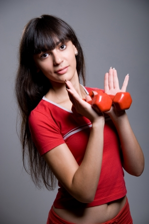 Fitness woman with dumbbells. Sport. Isolated on gray background. Stock Photo - 15484276