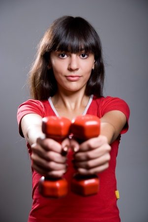Young lady doing workout with dumbbells on the gray background Stock Photo - 15484275