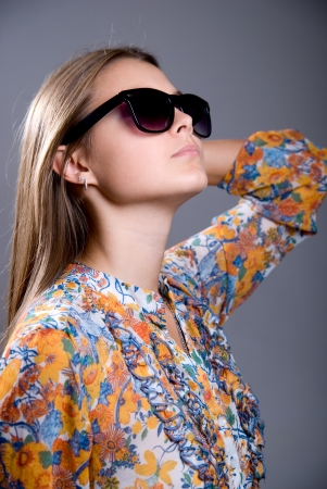 Portrait of a girl wearing sunglasses on a gray background photo