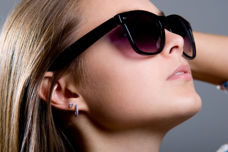 Portrait of a beautiful girl in sunglasses on a gray background Stock Photo