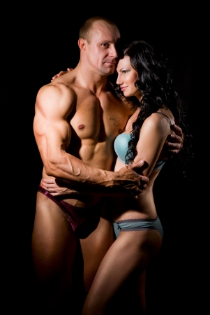 Muscular man and a woman on a dark background