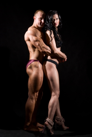 Muscular man and a woman posing in studio on dark background photo