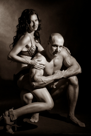 Muscular man and a woman posing in studio on dark background toning photo