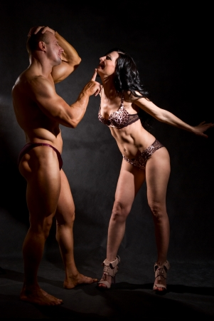 Muscular man and a woman posing in studio on dark background Stock Photo