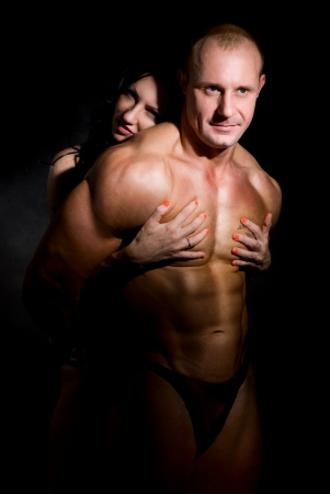 Woman hugging muscular man on a dark background Stock Photo