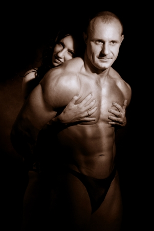 Woman hugging muscular man on a dark background photo