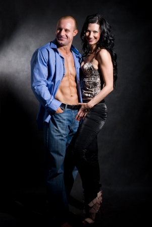 Muscular handsome sexy man with pretty woman on dark background photo