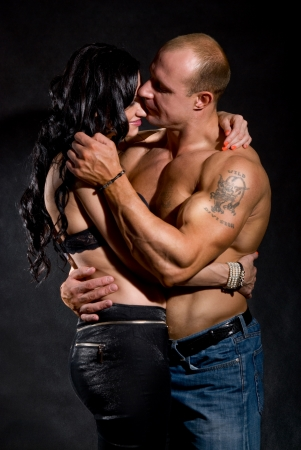 Muscular man and a woman on a dark background Stock Photo - 16306369