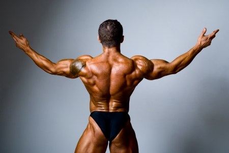 male bodybuilder: Young bodybuilder showing his biceps on a gray background Stock Photo