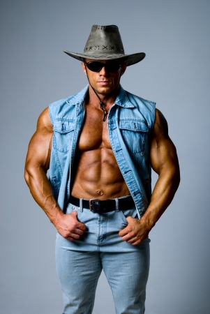 Muscular man in a cowboy hat on a gray background Stock Photo