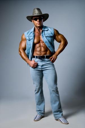 Muscular man in a cowboy hat on a gray background Standard-Bild