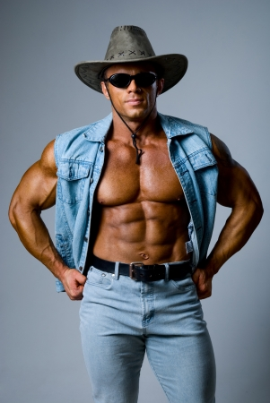 Muscular man in a cowboy hat on a gray background photo