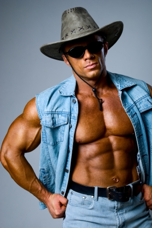 Handsome muscular man in a cowboy hat on a gray background photo