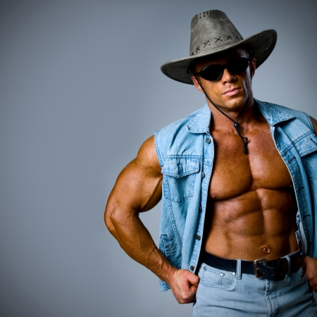 A handsome man in a cowboy hat on a gray background Stock Photo