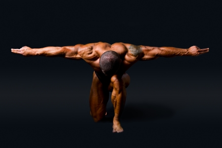hombre fuerte: Muscular hombre con los brazos extendidos a los lados y la cabeza down.isolated sobre un fondo negro