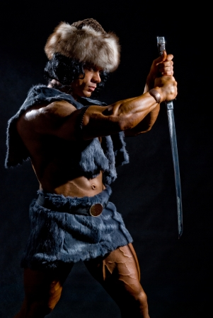 Male warrior with a sword in the form of a barbarian on a black background
