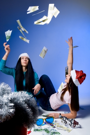 Girls in Santa hats, throw up banknotes.blue background photo