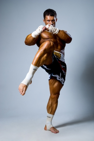 kickboxer: Kick-boxer training before fight on a gray background Stock Photo
