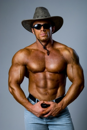 Muscular male in a hat and sunglasses on a gray background