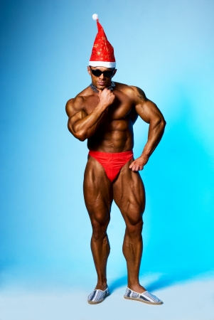 strong athletic man in a cap of Santa Claus.On a blue background