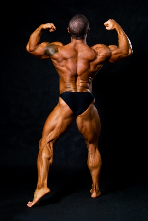 bodybuilder man: Tanned bodybuilder shows muscles of arms and back in black studio Stock Photo