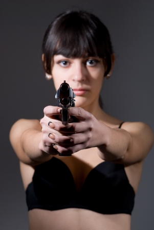 Young woman holding a gun on dark background Stock Photo - 17130585