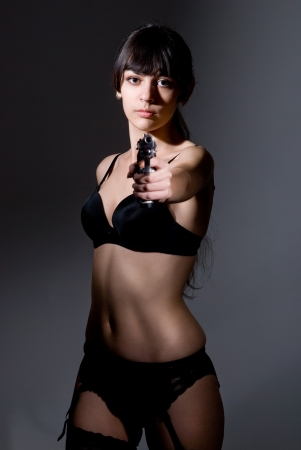 elegant fashionable woman with a pistol in hands. photo