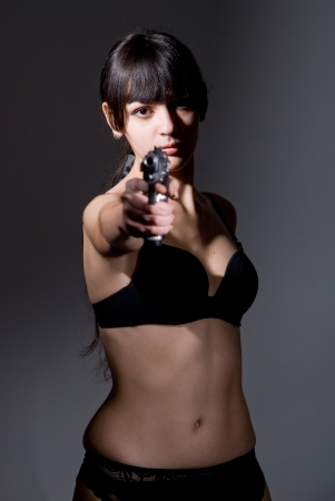 Shot of a sexy military woman posing with guns. Stock Photo - 17130639
