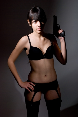 Girl in lingerie with a gun on a dark background Stock Photo - 17130554