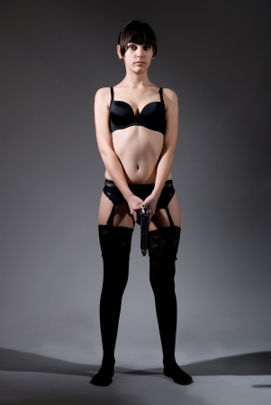 Full-length portrait of a girl with a gun in his underwear. photo