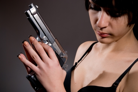 Close-up portrait of sexy woman with gun. photo
