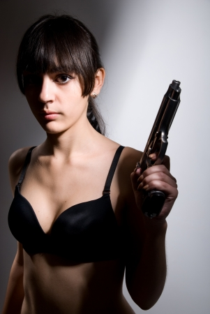 Portrait of a sexy girl with a gun. photo