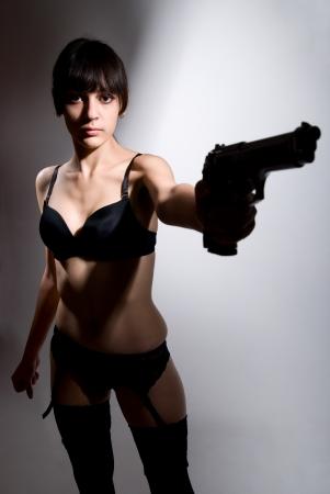 Sexy woman holding gun on gray. photo