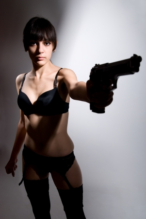 Sexy woman holding gun on gray. Stock Photo - 17130551