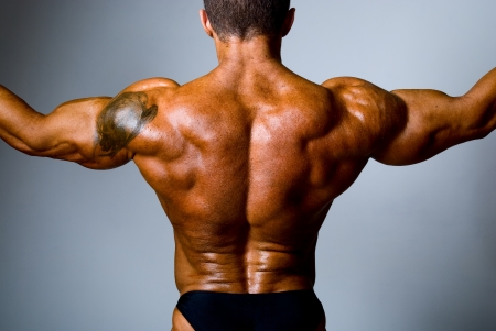 The back muscular man with a tattoo on her shoulder. photo