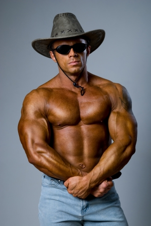 Handsome muscular man with a hat on a gray background photo