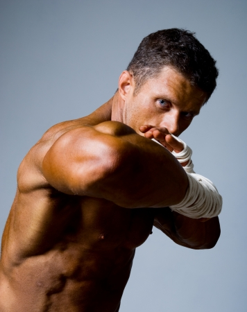 Close-up portrait of a kick-boxer in a fighting stance. Kickboxing or muay thai Stock Photo - 17232189
