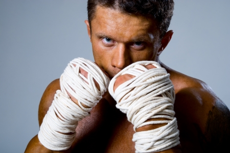 Close-up portrait of a kick-boxer in a fighting stance. Kickboxing or muay thai photo