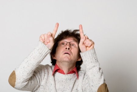 Man with disheveled hair pointing two fingers at something interesting over light background photo