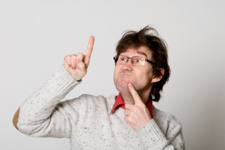 unresolved: Man with glasses and with disheveled hair pointing at something interesting over light background